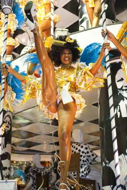 BRA0827AW South America, Rio de Janeiro, Rio de Janeiro city, a high-kicking costumed dancer with a comb in her hair at carnival in the Sambadrome Marques de Sapucai