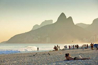 BRA0856AW South America, Rio de Janeiro, Rio de Janeiro city, Ipanema, sunbathers on Ipanema beach with the Dois Irmaos mountains in the background