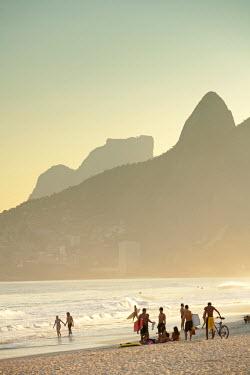 BRA0857AW South America, Rio de Janeiro, Rio de Janeiro city, Ipanema, sunbathers on Ipanema beach with the Dois Irmaos mountains in the background