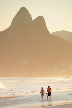 BRA0859AW South America, Rio de Janeiro, Rio de Janeiro city, Ipanema, a couple walking through the surf holding hands on Ipanema beach with the Dois Irmaos mountains in the background