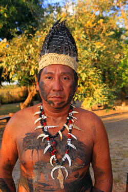BRA0936AW South America, Brazil, Miranda, Terena indigenous man from the Pantanal in a feather headdress wearing a bone and peccary tooth necklace