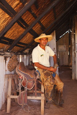 BRA0952AW South America, Brazil, Mato Grosso do Sul, Fazenda 23 de Marco, pantaneiro ranch holding a horn cup and dressed in leather chaps sitting next to a hand-made leather saddle