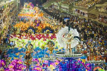BRA0955AW South America, Rio de Janeiro, Rio de Janeiro city, costumed dancer in a feather headdress and the floats and dancers of the Caprichosos samba school at carnival in the Sambadrome Marques de Sapucai