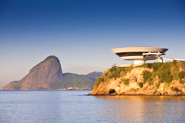 BRA1080AW South America, Rio de Janeiro, Niteroi, Oscar Niemeyer's Contemporary Art Museum (MAC Niteroi) in the late afternoon light, with Guanabara Bay and the Sugar Loaf (Pao de Acucar) in the background