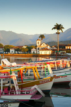 BRA1085AW Brazil, Parati, the Portuguese colonial town centre and the church of Saint Rita of Cascia seen from the water with fishing boats on the quay in the foreground