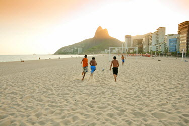 BRA1119AW South America, Rio de Janeiro, Rio de Janeiro city, Ipanema, boys playing football on Ipanema beach in front of the Dois Irmaos mountains