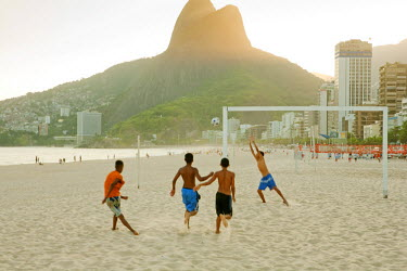 BRA1120AW South America, Rio de Janeiro, Rio de Janeiro city, Ipanema, boys playing football on Ipanema beach in front of the Dois Irmaos mountains
