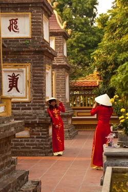 VN02221 Girls wearing Ao Dai dress, Tran Quoc Pagoda, West Lake (Ho Tay), Hanoi, Vietnam (MR)