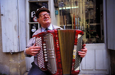HMS054843 France, Dordogne, Perigord Noir, Sarlat, Jacky Porret and his accordion in front of his fishing bar