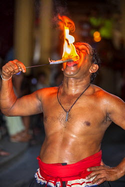 SRI1573 A Kandyan fire eater shows no sign of pain as he places a flame on his tongue during a display of Kandyan and Low Country dances at Kandy, Sri Lanka
