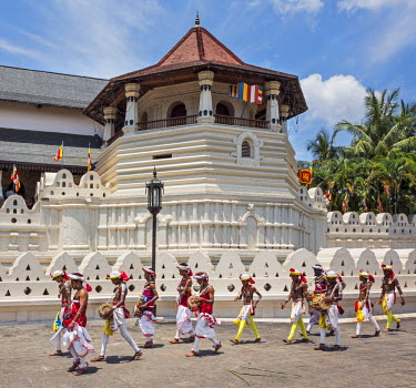 SRI1617 Kandyan dancers and drummers pass in front of the Temple of the Sacred Tooth Relic on their way to participate in the Kandy day Perahera which is a magnificent procession through the city�s streets, S...