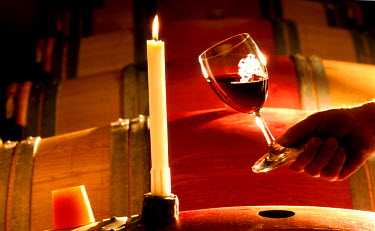 HMS302796 France, Gironde, Lalande de Pomerol, Bordeaux vineyard, Chateau Garraud of Nony vineyard, AOC Lalande de Pomerol, glass of red wine and silicone bunghole with candle light in the wine store barrels