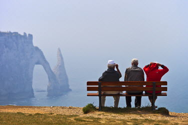 FRA7668 Two old caucasian men and an old caucasian women on a bench look out towards the sea stack and sea arch Porte d'Aval of the Falais Aval with the English Channel in the background,  Etretat, Haute Norm...