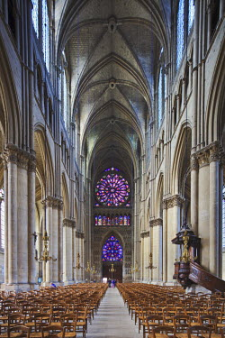 The main aisle and 2 rose windows at the west end of the interior of Notre Dames de Reims, Reims, Champagne Ardenne, France.