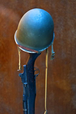 FRA7684 A World War 2 American army helmet atop a vertically placed M1 Garand rifle, USA. Caliber .30-06 at the Normandy American Cemetery and Memorial, Omaha Beach, Colleville sur Mer, Basse Normandie, Franc...
