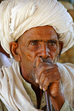 India, Rajasthan, Ajabgarh. A turbanned village man smokes a long pipe.