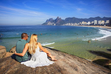 BRA1458AW Couple sitting on Ponta do Aproador overlooking Ipanema beach, Rio de Janeiro, Brazil (MR)