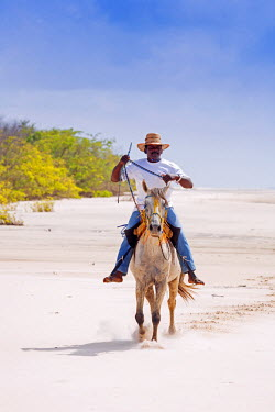 BRA1580AW South America, Brazil, Para, Amazon, Marajo island, local man on horseback riding barefoot on the beach near Soure