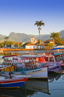 BRA1035AW Brazil, Parati, the Portuguese colonial town centre and the church of Saint Rita of Cascia seen from the water with colourful fishing boats in the foreground