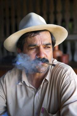 BRA1632AW South America, Brazil, Goias, Pirenopolis, a man smoking a Corn Husk Cigarette in the Fazenda Babilonia sugar mill near Pirenopolis, PR, MR