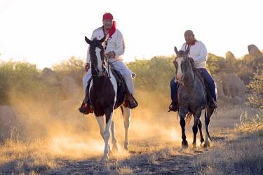 USA8504AW Two Apache Indians on horseback at the Apache Spririt Ranch near Tombstone, riding through the desert, Arizona, USA MR
