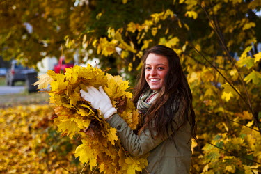 AR4624200063 Sandpoint, Idaho, USA. A Athletic Young Woman Smiling Holds A Large Pile Of Orange Leaves In The Fall In Idaho.