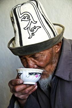 AR4661200018 Karakul, Tajikistan. Kyrgyz Man Drinking Tea, Karakul Lake, Tajikistan.