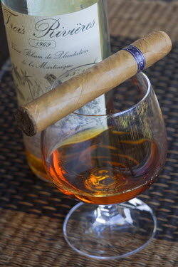 HMS237701 Caribbean, Martinique (French West Indies), Le Francois, Le Cap Est Lagoon Resort and Spa, luxury hotel, Le Cohi Bar, close up of a glass of Trois Rivieres aged rum of 1969 and Punch Habana cigar