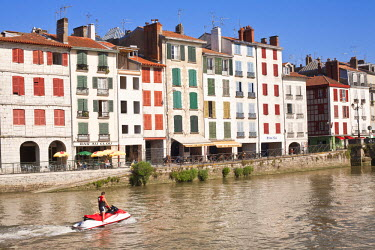 HMS544975 France, Pyrenees Atlantiques, Bayonne, Quai Galuperie, jet ski in front of traditional houses on Nive River banks