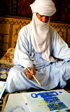 HMS0575120 Algeria, Sahara, Hoggar (Ahaggar Mountains), Tamanrasset, Tuareg man in his working room with its texts and calligraphies