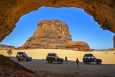 CHA0065 Chad, Gaora Hallagana, Ennedi, Sahara. 4x4 vehicles are parked in the shade of a massive rock shelter while visitors look for rock art.