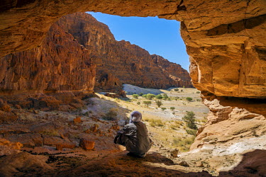 CHA0075 Chad, Elikeo, Ennedi, Sahara. A Toubou man looks out of a massive sandstone cave.