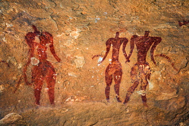 CHA0080 Chad, Elikeo, Ennedi, Sahara. Three broad-shouldered faceless red figures, one with the outline of a headdress.