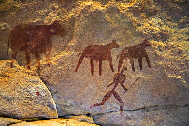 CHA0099 Chad, Taore Koaole, Ennedi, Sahara. A painting of cattle and a man running with a stick or club in hand decorate the sandstone wall of a cave.