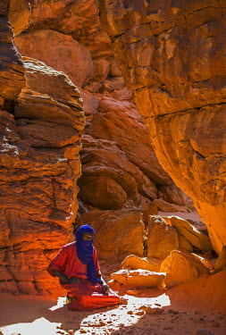 CHA0116 Chad, Abaike, Ennedi, Sahara. A Toubou tribesman squats among weathered red Palaeozoic sandstone rocks.