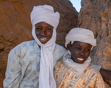 CHA0152 Chad, Barakatra, Ennedi, Sahara. Two young Tubu boys fresh from riding their horses relax among rocks.