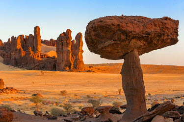 CHA0158 Chad, Chigeou, Ennedi, Sahara. Weathered red sandstone in a desert landscape with a large mushroom-like feature of balancing rock.