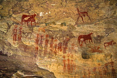 CHA0188 Chad, Terkei West, Ennedi, Sahara.  An ancient rock art panel of human figures with large decorated hairstyles and domesticated animals.