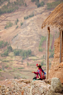 PER33691AW South America, Peru, Cusco, Sacred Valley, Pisac. A Quechua woman in a montera hat and with a K'eperina shawl looks out over the Sacred Valley from the hills above Pisac