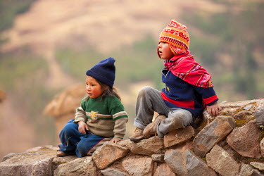 PER33692AW South America, Peru, Cusco, Sacred Valley, Pisac. Quechua children, one wearing a chullo at the Pisac ruins in the hills above the Urubamba valley. The first chullo that a child receives is traditiona...