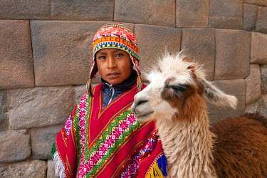 PER33704AW South America, Peru, Cusco. A Quechua boy in a poncho and a chullo woollen cap with a Llama standing in front of an Inca wall in the UNESCO World Heritage listed former Inca capital of Cusco