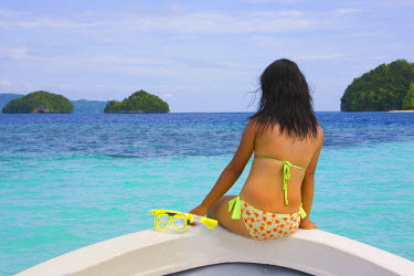 OC16KSU0049 Tourist sitting on boat bow watching landscape, Rock Islands, Palau, Micronesia, Pacific Ocean