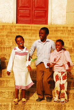 AF56AAS0009 Eritrea, Asmara, three African kids jumping on stairs in joy