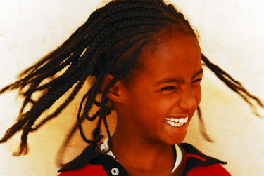 AF56AAS0023 Eritrea, Asmara, happy African girl tossing her braided hair against wall (MR)