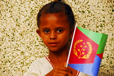 AF56AAS0031 Eritrea, Asmara, close-up portrait of an African girl holding a UNICEF flag against wall