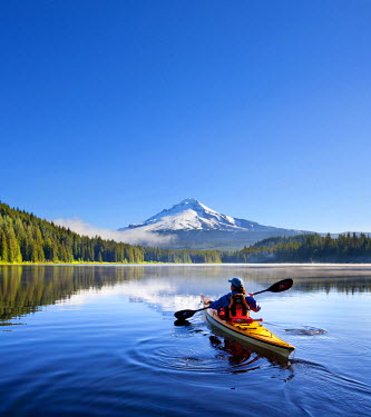 US38GLU0033 USA, Oregon. A woman in a sea kayak paddles on Trillium Lake, Oregon, in the Oregon Cascades, with a Mt. Hood backdrop (MR)