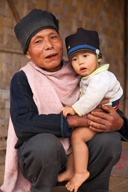 LAO1082 Laos, Houayla. An Akha man dandling his grandson on his knee.