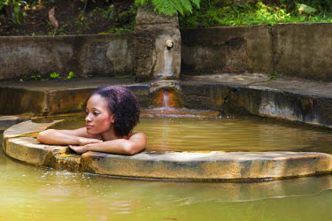DOM0051AW Dominica, Roseau. A young woman relaxes in the natural springs at Papillote Wilderness Retreat. (MR).