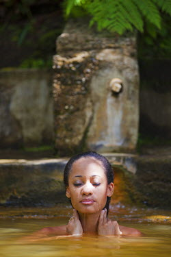 DOM0052AW Dominica, Roseau. A young woman relaxes in the natural springs at Papillote Wilderness Retreat. (MR).