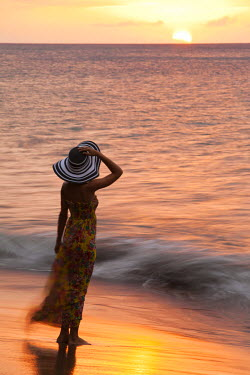 DOM0066AW Dominica, Portsmouth. A young woman watches the sun set from Coconut Beach. (MR).